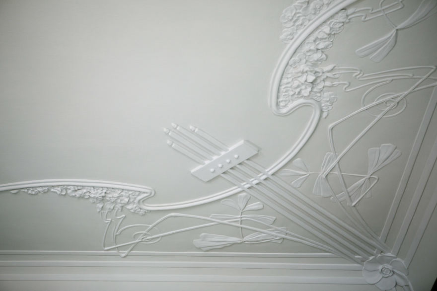Moteriškojoje pusėje esanti muzikinė menė buvo dekoruota ilgomis, elegantiškomis linijomis ir gėlių žiedais. Ir jokių stačių kampų, net kambario sienų ir lubų sujungimo kampai užapvalinti, puošti gėlėmis, instrumentų stygomis. Sienos buvo išmuštos pilku aksomu, ran